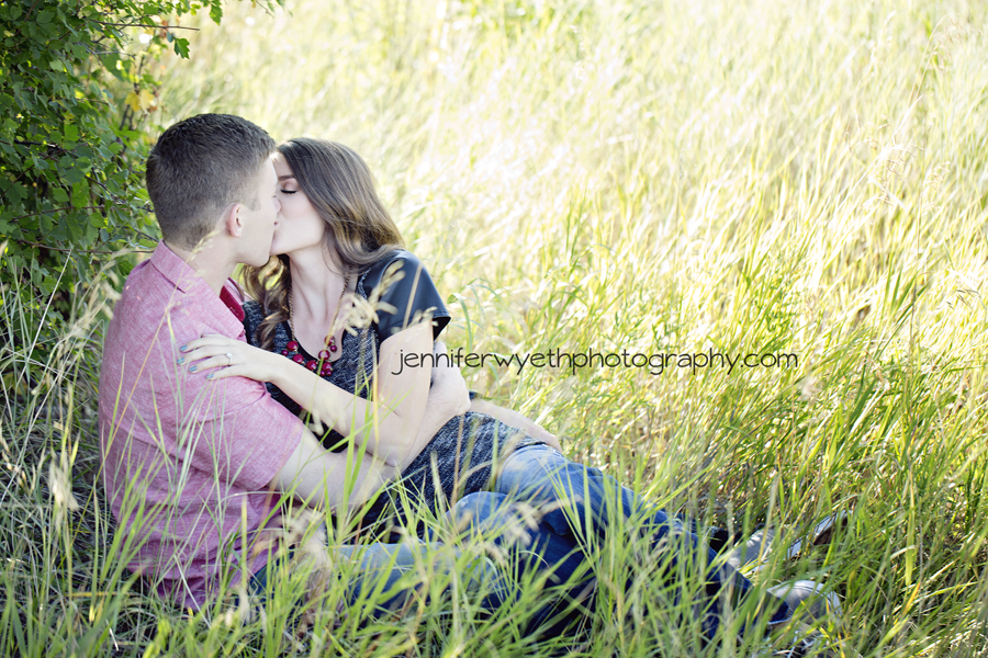 engaged couple kisses in the grass