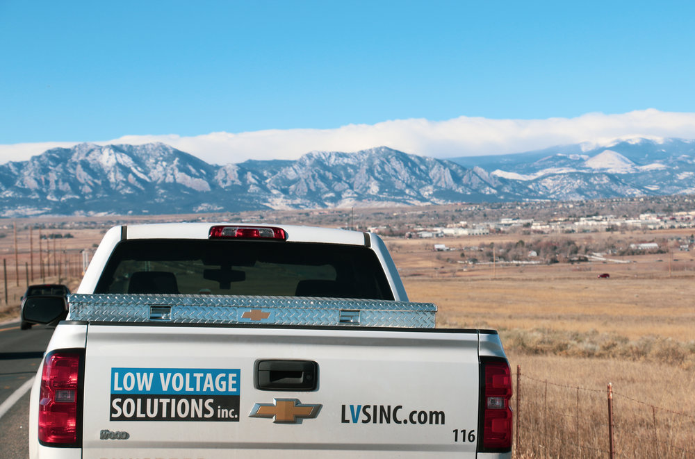 Low voltage solutions truck sits before a majestic colorado mountain scene.