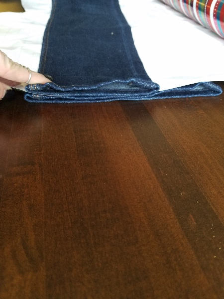 Both pairs are lined up on the inseam with the paper between them.