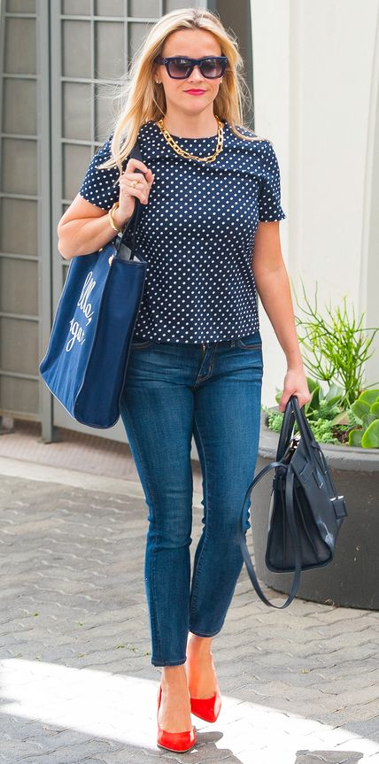 Reese Witherspoon is wearing the perfect cute and classic outfit. Her polka dot top is balanced by the structured jeans, classic sunglasses, stud earrings, and navy structured bags. Her link necklace is a little more classic. If the links were rounder they would be more fun, but the rectangles add nice balance to the polka dot top. . The red pop of color is also a fun but bold detail.