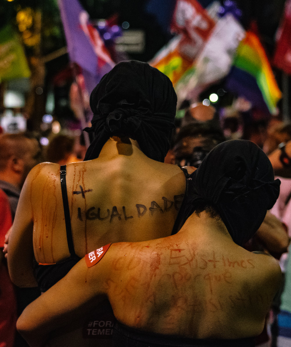 Performing artists in Rio embrace during a march for women's rights.  Igualdade  (equality) is written on the exposed back of one of the protesters.