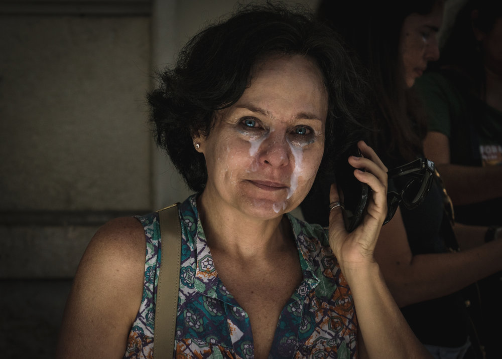 A woman calls a family member after being exposed to tear gas during a protest. Milk of Magnesia is used by demonstrators to counteract the chemicals in the gas that cause irritation and burning to the eyes.