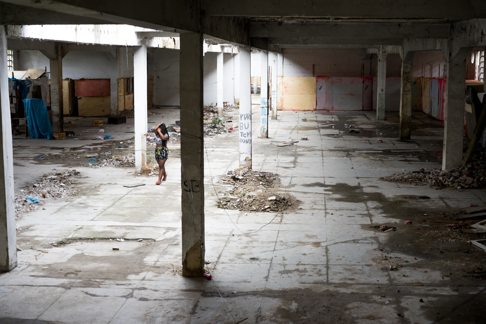 A resident of the former Ministry of the Economy building walks through a hall that used to contain several unoficial apartments for the city's poor. (Photo: C.H. Gardiner)