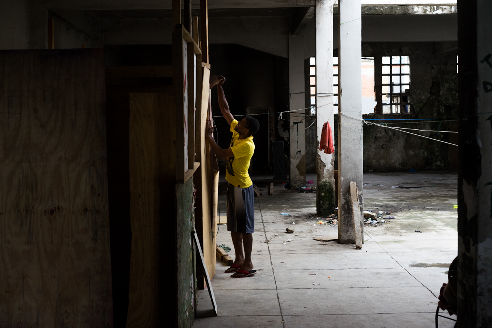 A resident of the former Ministry of the Economy building takes apart the wooden boards that used to make up the walls to his ad hoc apartment. (Photo: C.H. Gardiner)