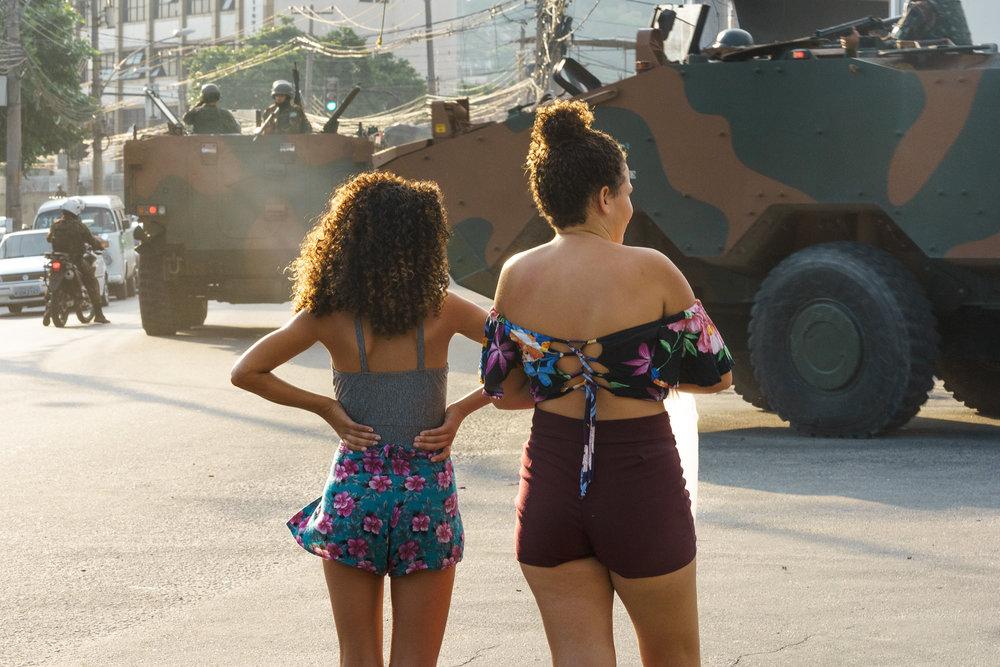 Residents of Complexo de Alemao look on as a army convoy passes Saturday, September 15, 2018 in Rio de Janeiro.