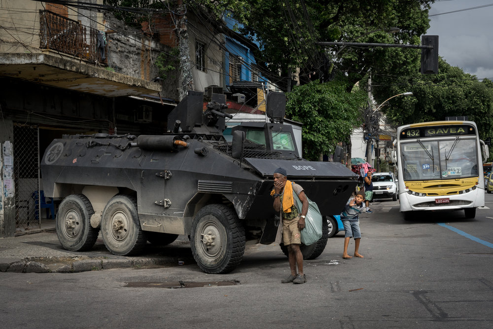 A boy uses an APC belonging to the BOPE special operations unit as a prop to tease a homeless man during a police operation in Rio de Janeiro, August 8, 2018.