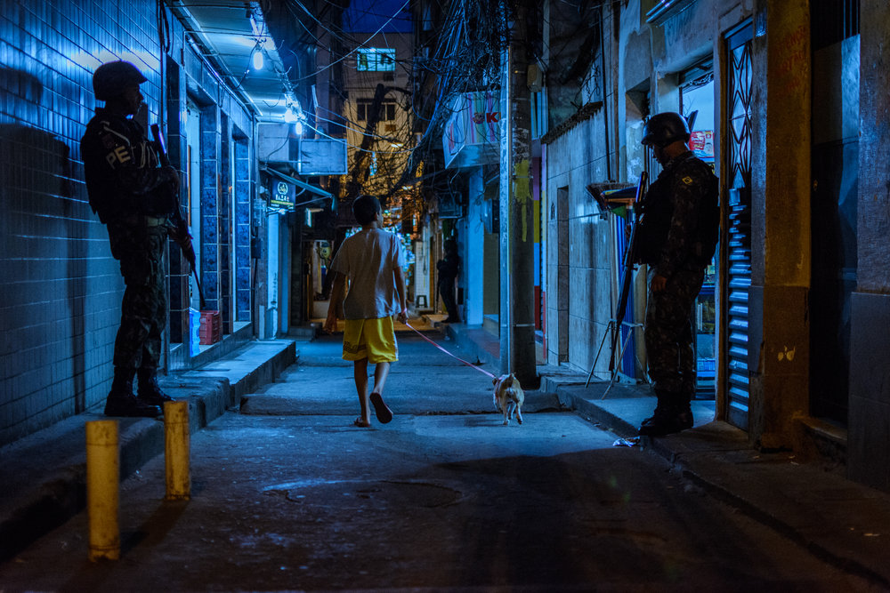 A boy walks his dog between members of Brazil's armed forces in Rocinha favela, Rio de Janeiro, Sept. 22, 2017. This use of the military in Rocinha favela became the template for future operations during the intervention.