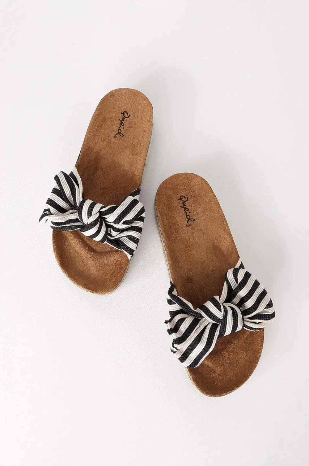 Pair the Dana Point Black and White Striped Espadrille Slide Sandals with cut-off shorts and head out to the beach! A fabric black and white striped toe strap has a cute bow detail, above a soft suede contoured insole, and trendy cork and espadrille outsole. Slide-on design.