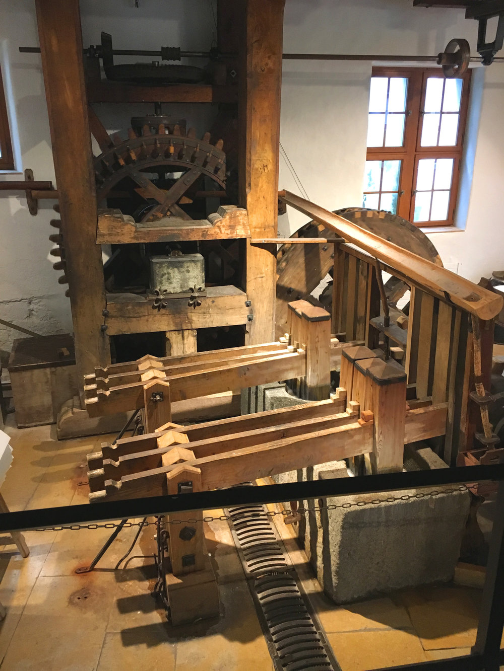 The mighty wooden stamping units pounding the rag pulp, driven by the waterwheel's action