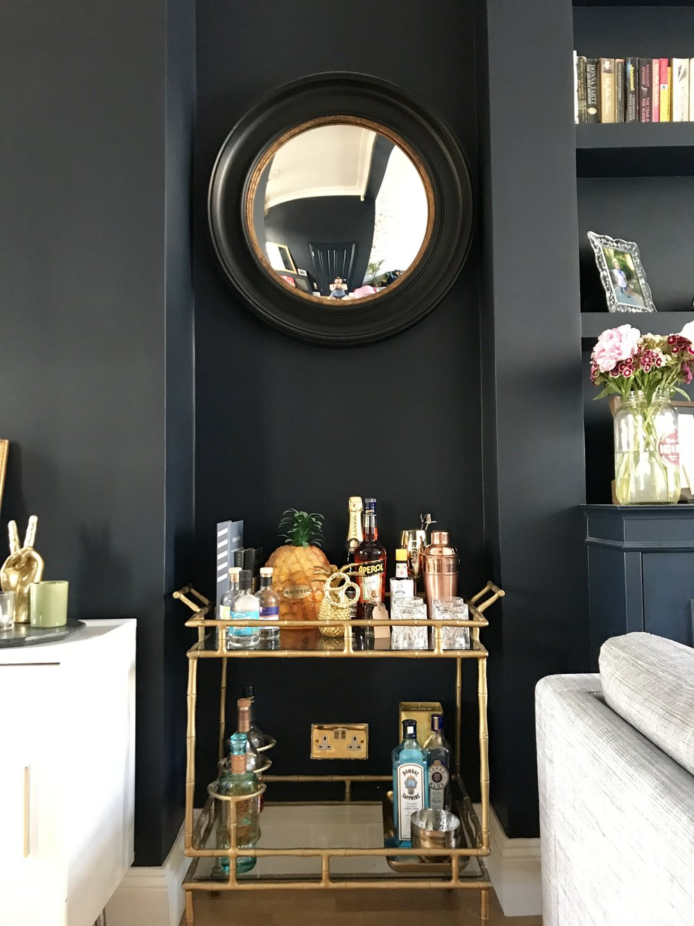 Mirror from Hurn & Hurn, Drinks trolley and gold pineapple from Oliver Bonas, Hammered metal tray and bowls from Sainsbury's
