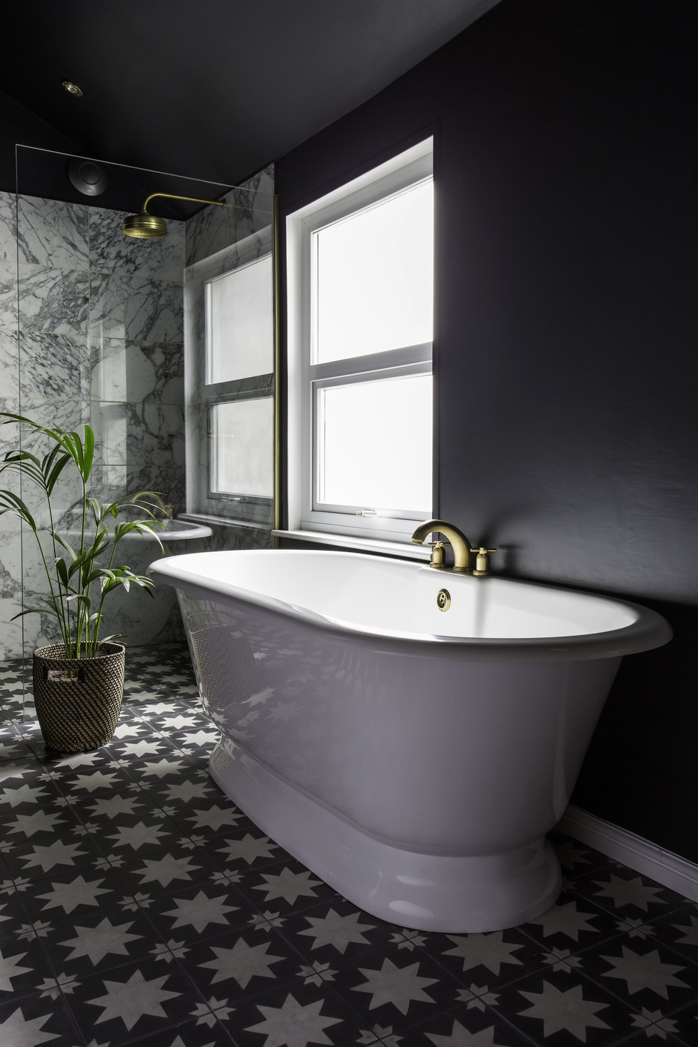 Hello sexy!  V+A Baths York bath ,  Perrin & Rowe shower and bath taps ,  Arabescato shower tiles from Topps Tiles , Pradena floor tiles  Bert & May  and walls in Farrow & Ball's Off Black. Photo: Kasia Fiszer