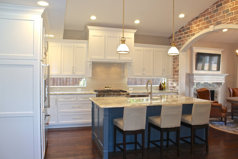 After: Large island with seating, antique brass fixtures, thoughtful design, brick archway, custom fireplace hearth