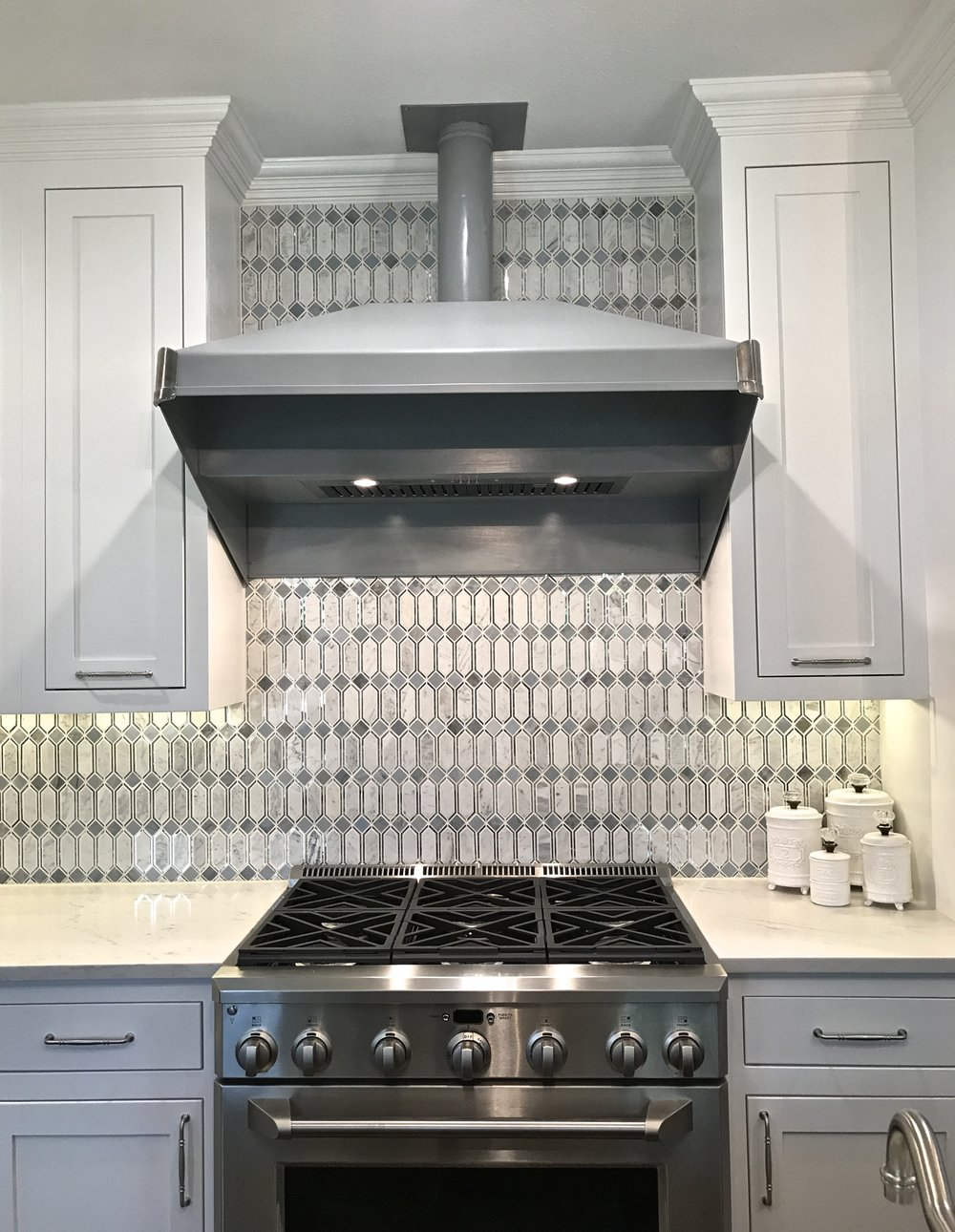 Original range hood, diamond cut marble and mirror tile modeled after stained glass from the 1920's.