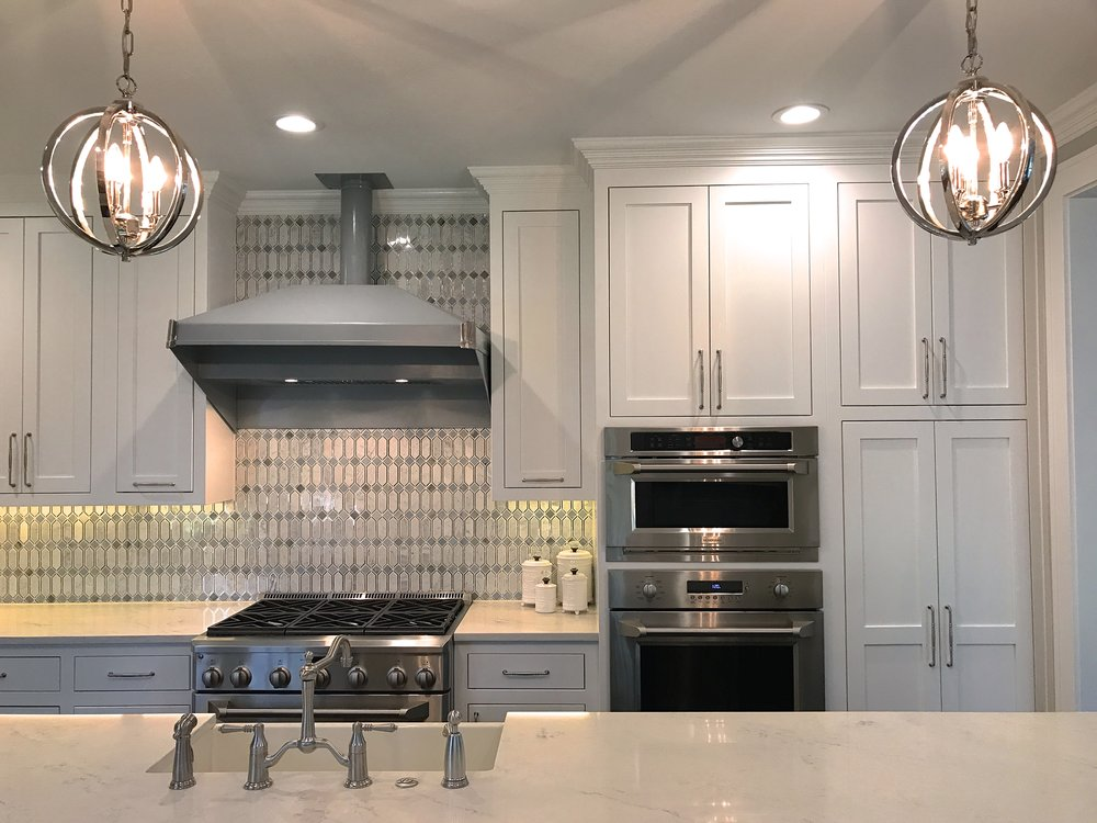 I always incorporate pendant lights over kitchen islands. This anchors the island and softens the angles a bit.