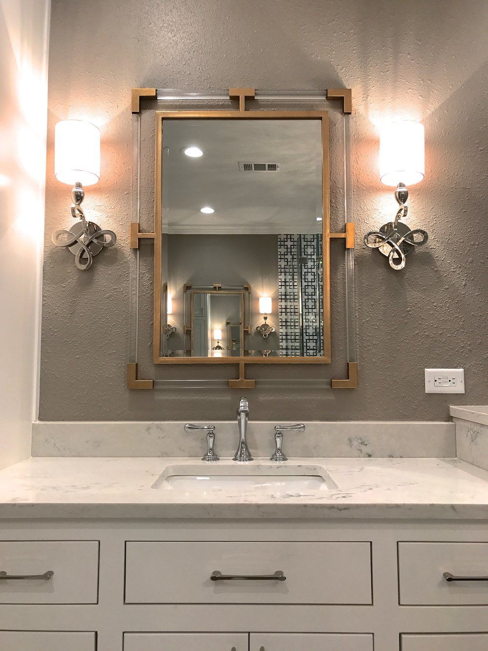 The shape of the gold leaf vanity mirror mimics the pattern in the marble wall tile. Again with the details.