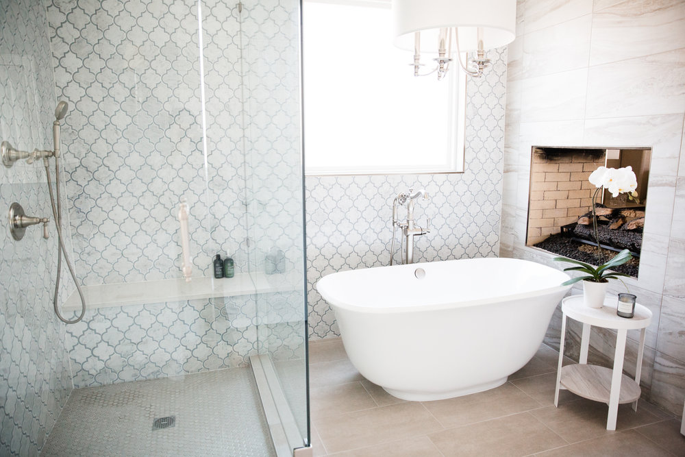 We gutted and reconfigured the master bathroom. The shower and tub walls are clad with marble mosaic from floor to ceiling. We recovered the double sided brick fireplace with 12x24 porcelain tile.