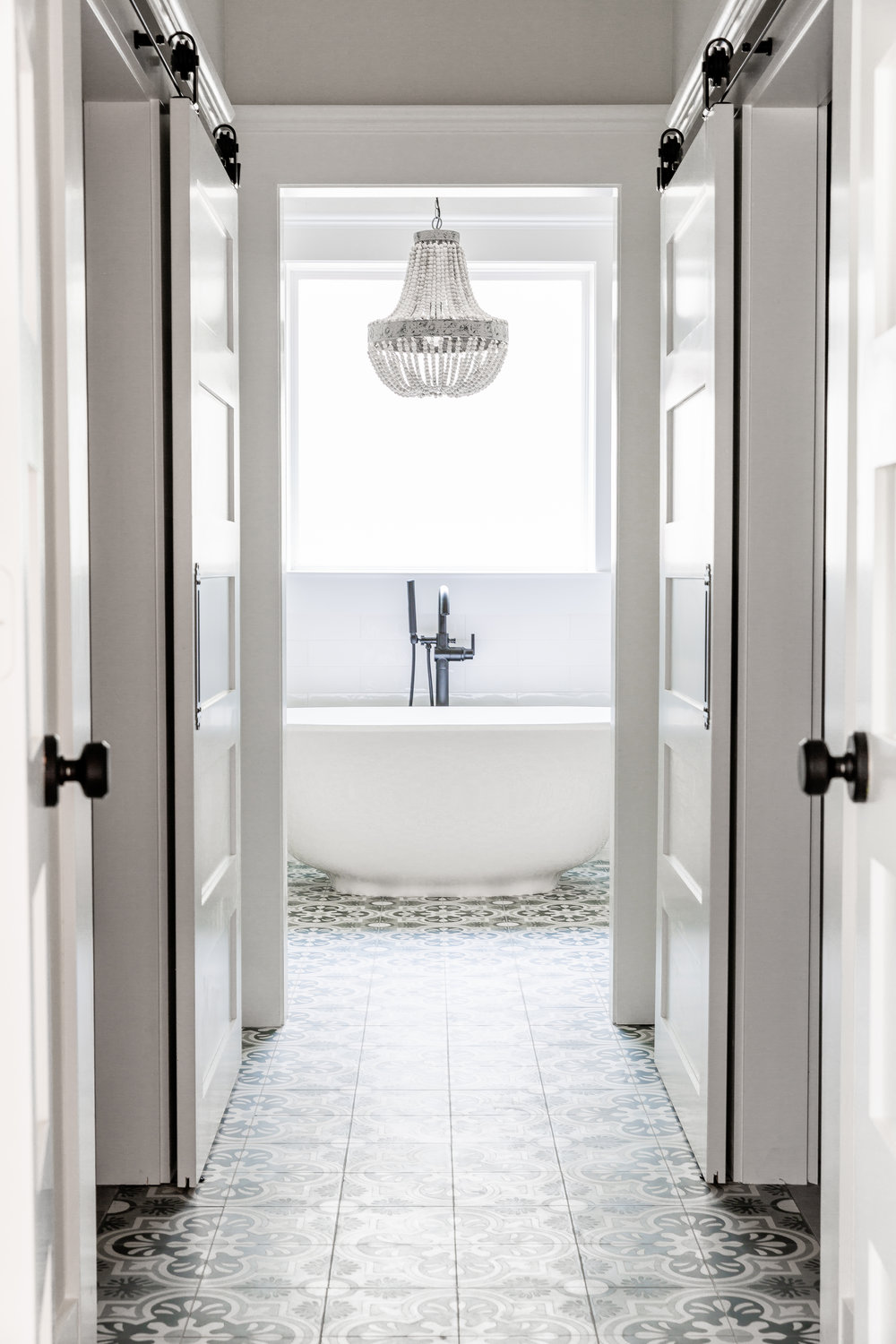 A hallway flanked by barn doors opening up to his & hers closets connects the master bathroom to the existing master bedroom. The bathtub is visible from the entry, anchored under a beaded chandelier by  Shades of Light .