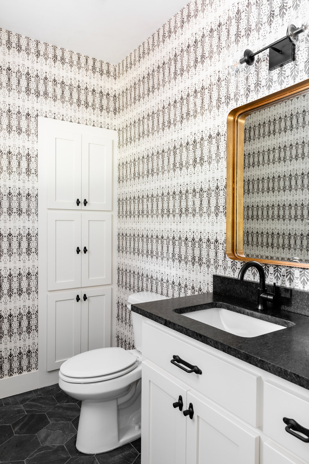 Get creative with your powder bathroom. These spaces are primarily used by guests, so I like to go the extra mile with a decorative element like this  Anthropologie  wall covering. We went for even more pattern on the floor with this slate hexagon tile from  The Tile Shop.