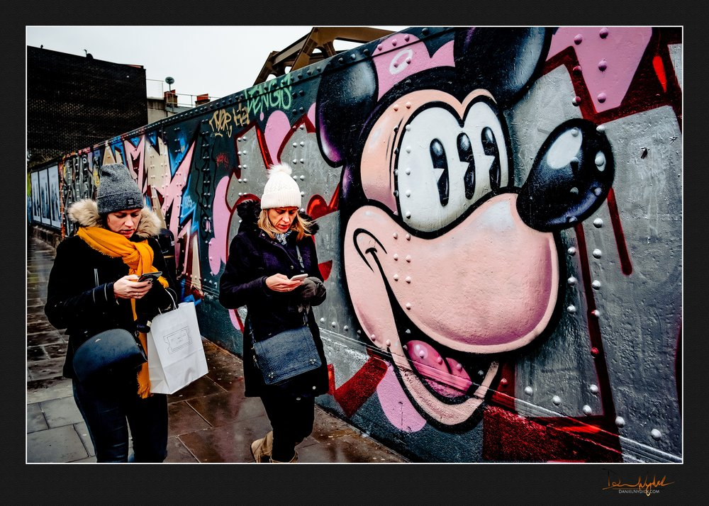 mickey mouse looking with three pupils at women not paying atten
