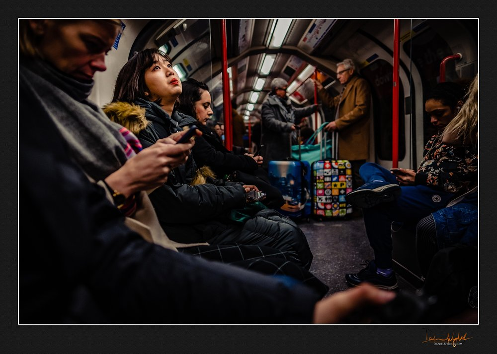 girl daydreaming looking up while riding the tube train
