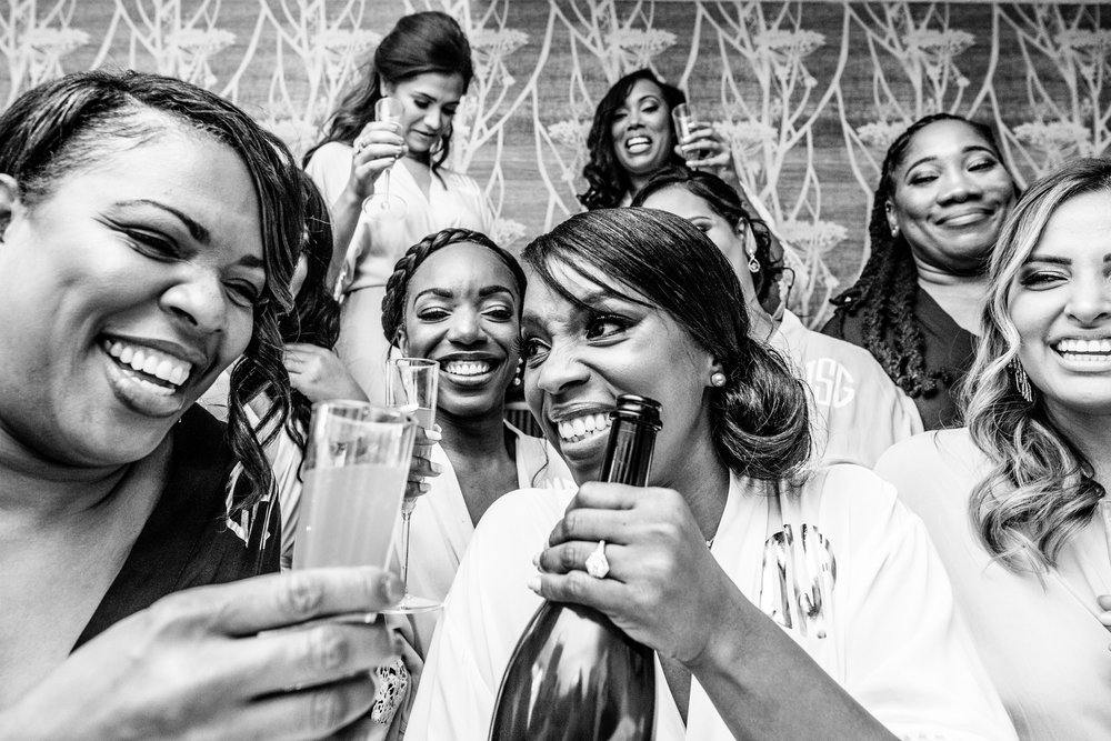 bridesmaids laughing while drinking mimosas in their robes