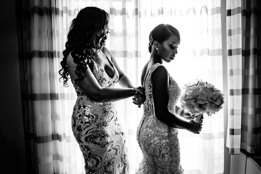 bridesmaid and maid of honor, sister, helping the bride into her