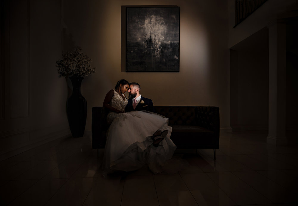 epic moody portrait of the bride and groom on the couch at the g