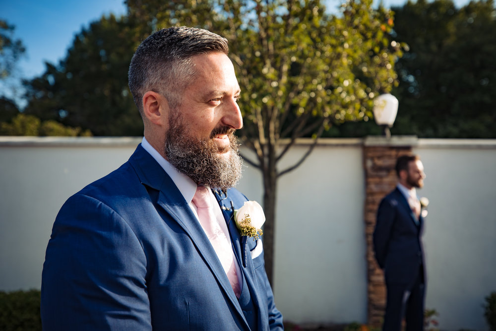 groom smiles as he sees his bride coming down the aisle at their