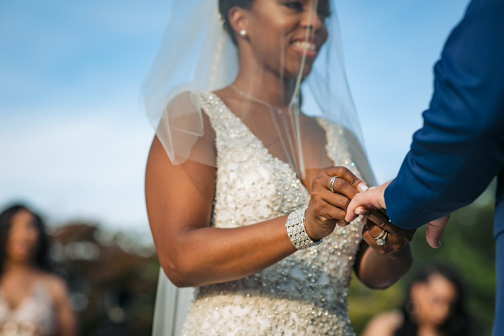bride smiling putting wedding ring on her groom