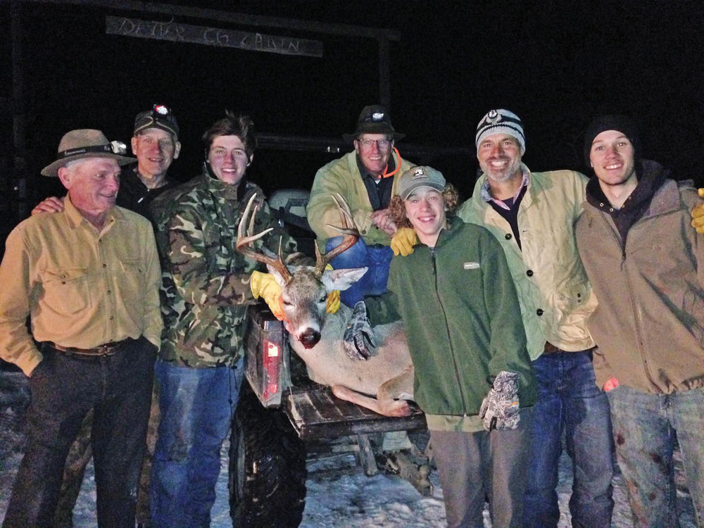 Quentin Favia shares the joy of his first whitetail with his camp.