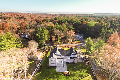 aerial view of New England home surrounded by autumn trees
