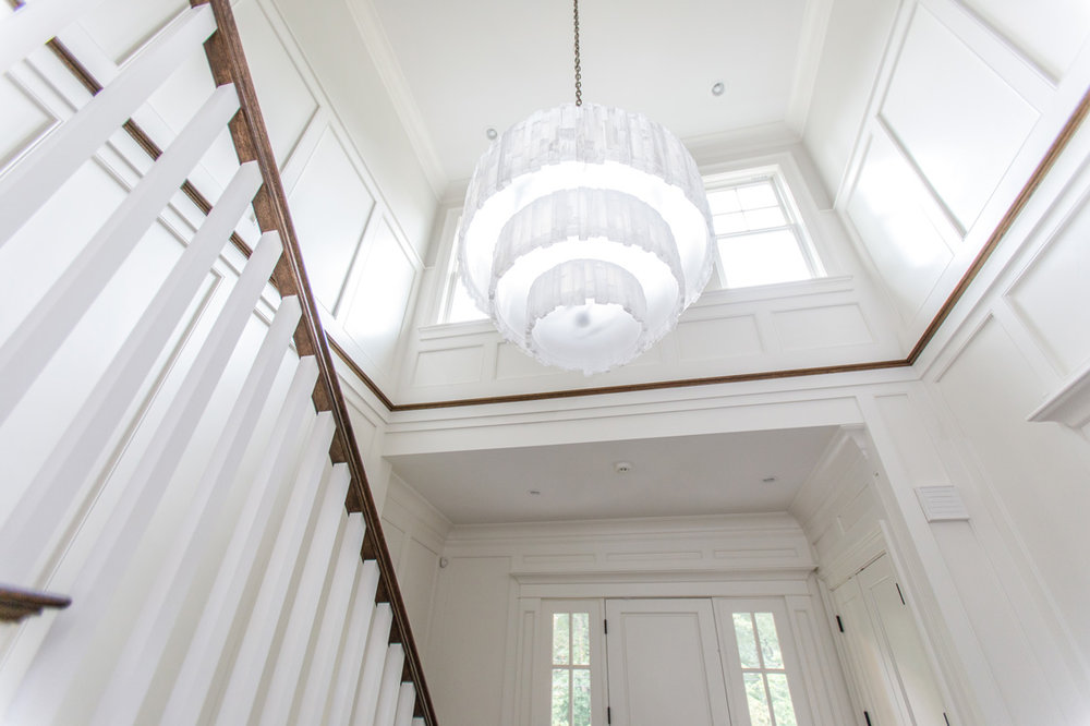 white entryway with chandelier and banister