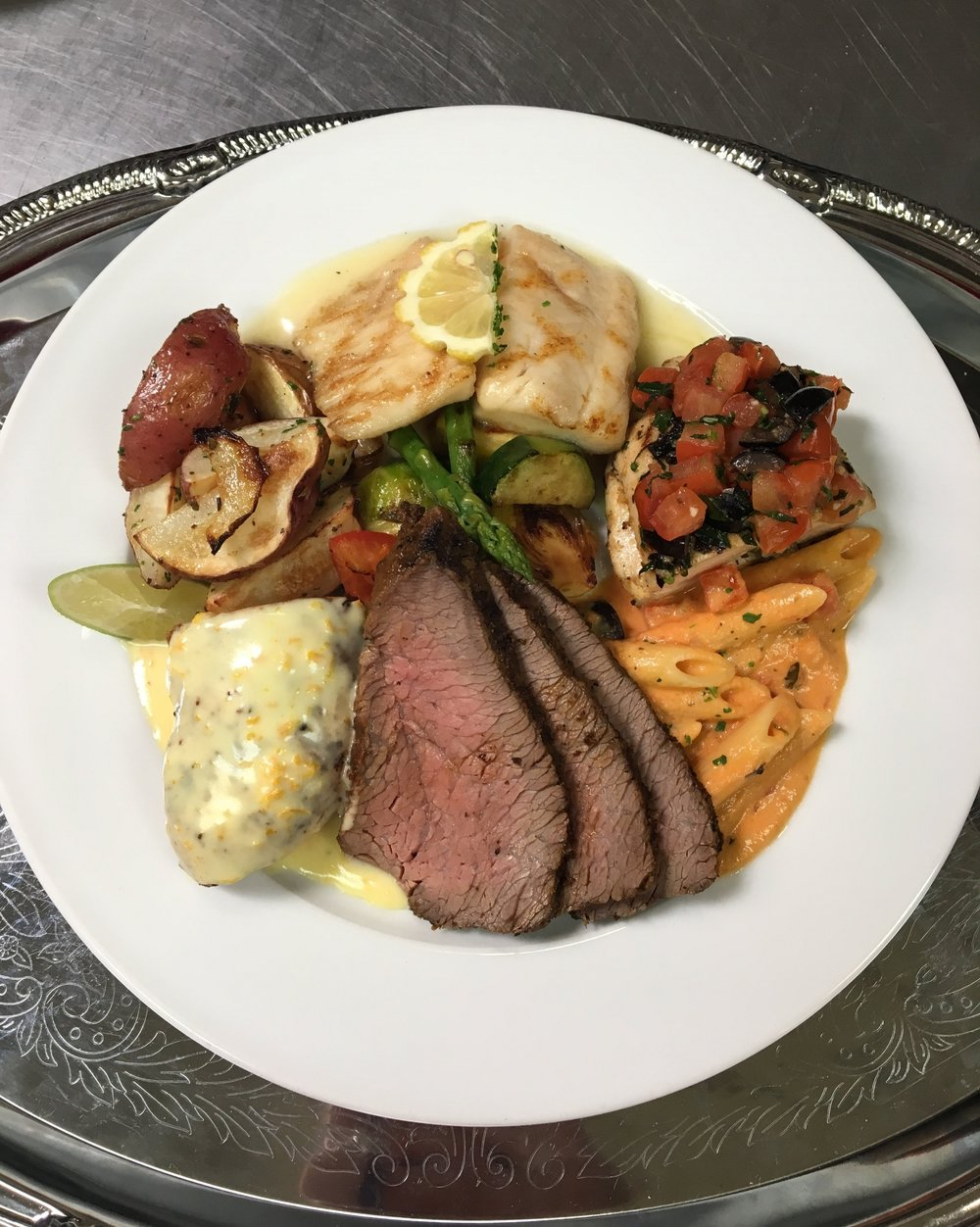 Wood Fired Prime Angus Tri Tip, Tequila Lime Chicken Breast, Herb Chicken Breast, Grilled Tilapia with Lemon Butter Sauce, Penne Mozzarella Pasta, Roasted Red Bud Potatoes, and Grilled Vegetables