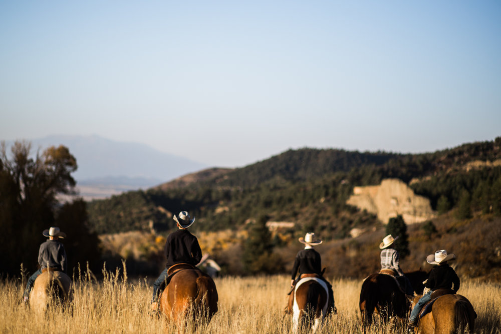 family riding horses on colorado cattle ranch
