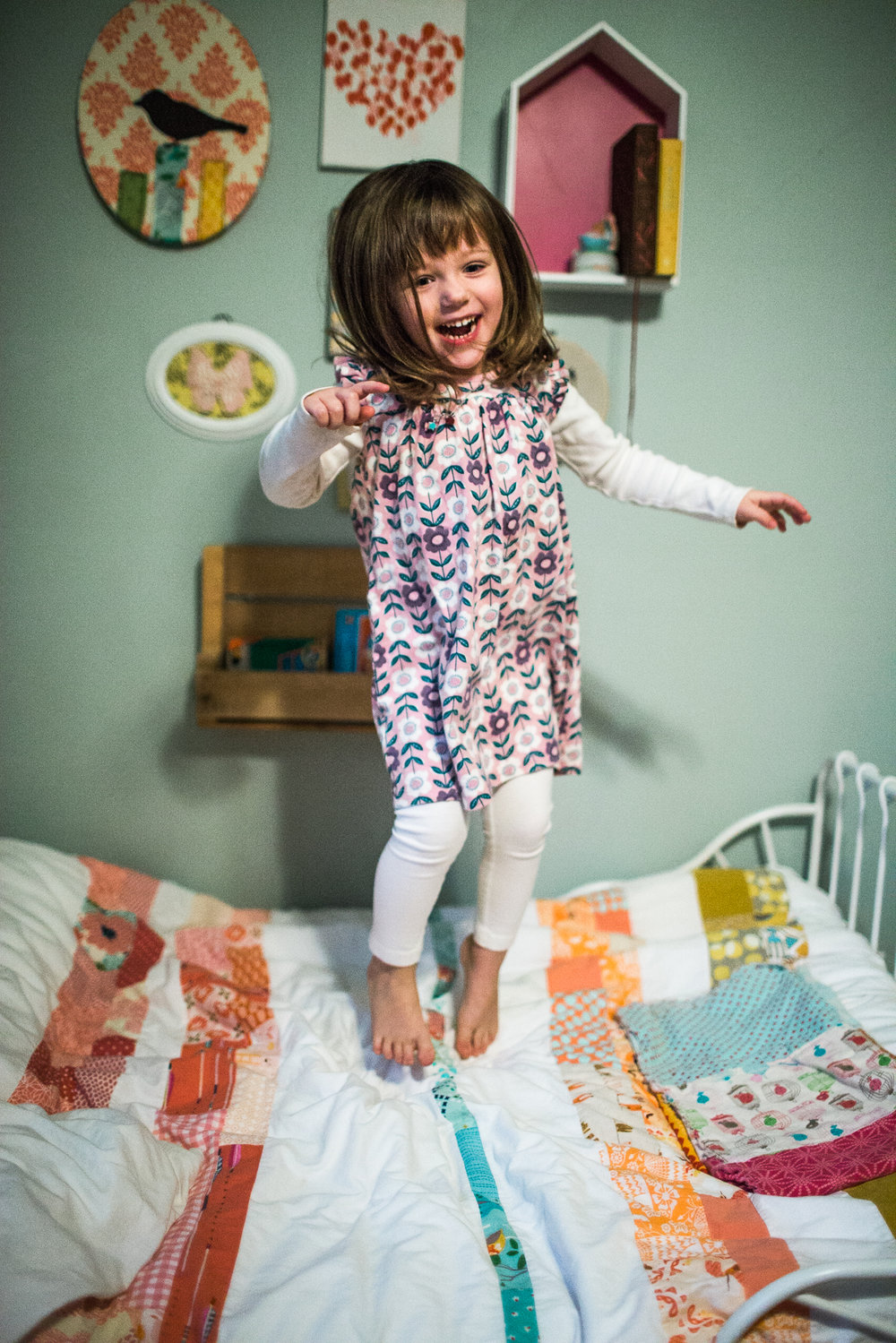 young girl jumping on bed in room