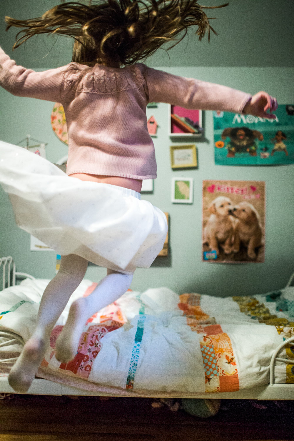 young girl jumps off bed twirling