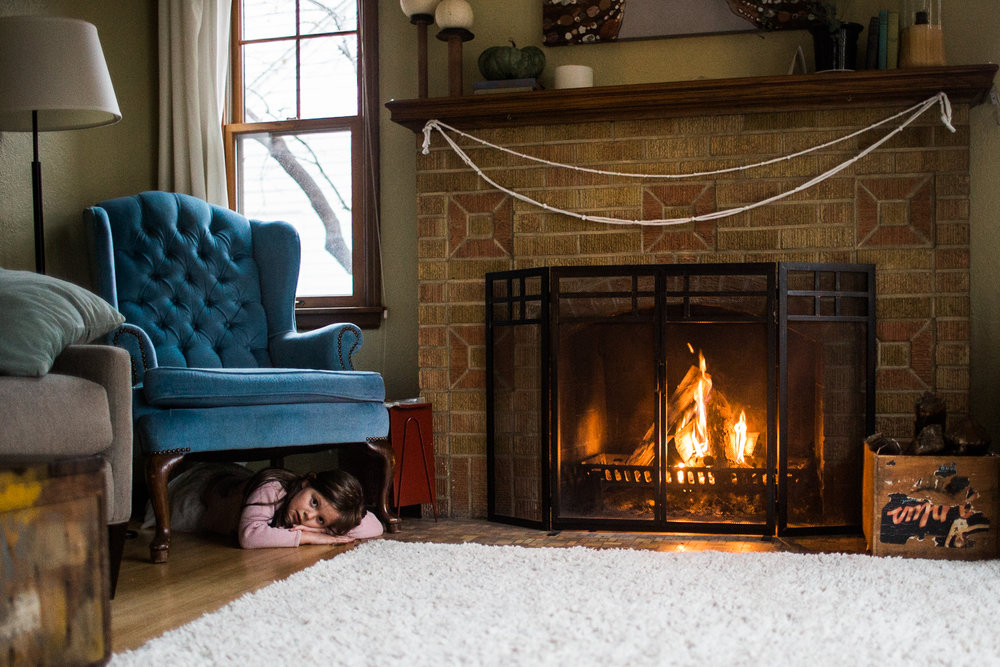 girl curls up by the fire place under chair in living room