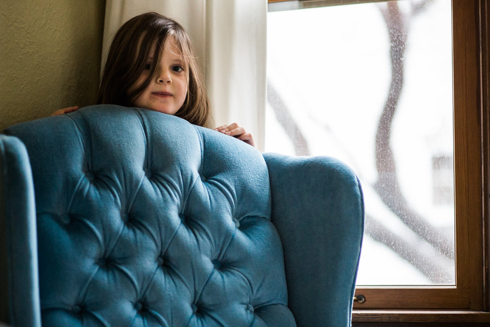 girl hides behind reupholstered chair