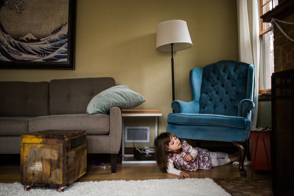 young girl hides under chair in home