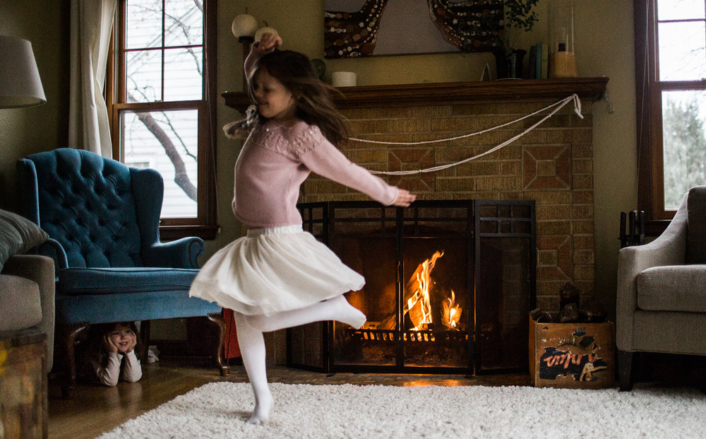 young girl dances to the nutcracker during christmas by the fire place