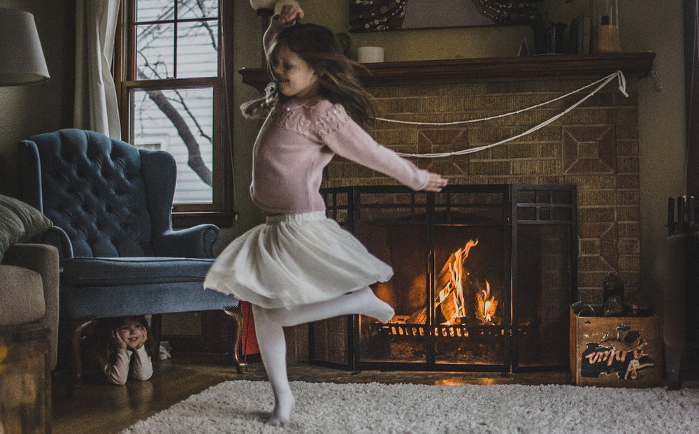 sisters dance and twirl by fireplace