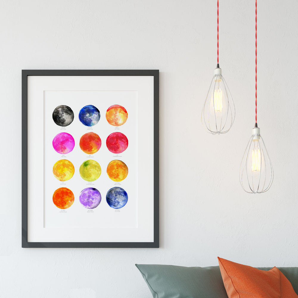 Art print by drawn together art featuring full moons name illustrations displayed on wall with hanging lights in front