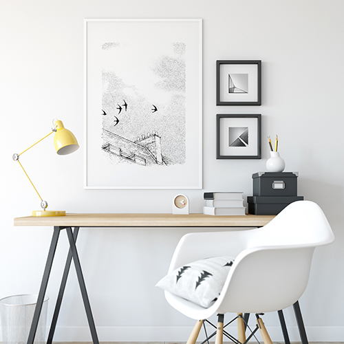 A desk and wall with a framed drawn together art collective print featuring swifts flying over rooftops