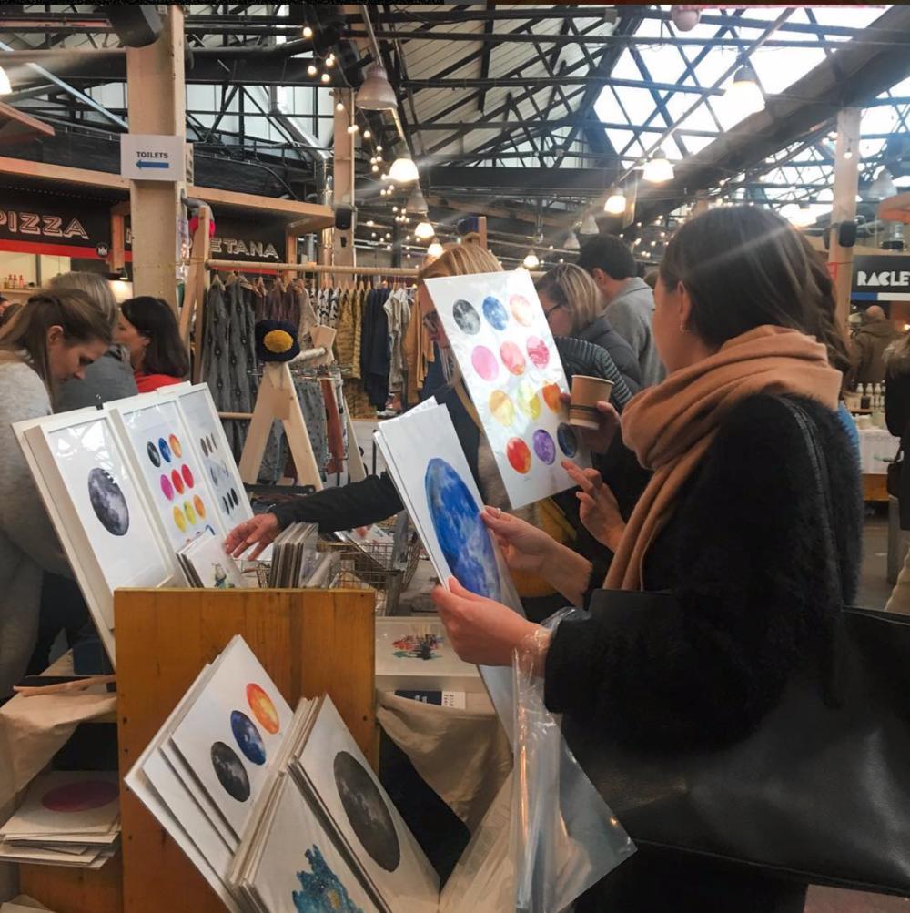 Woman looking at moon art prints by drawn together art at craft fair