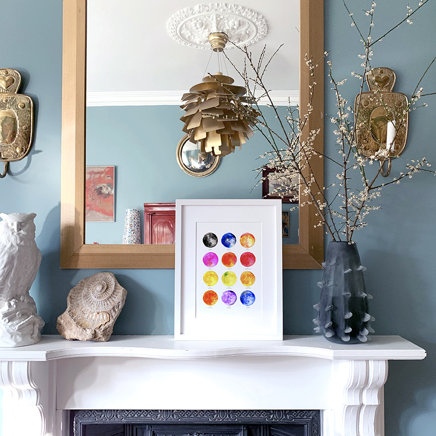 A colourful full moon names art print by drawn together art collective displayed on mantle piece in front of a mirror