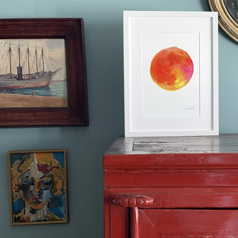 framed full moon artwork by drawn together art displayed on cabinet