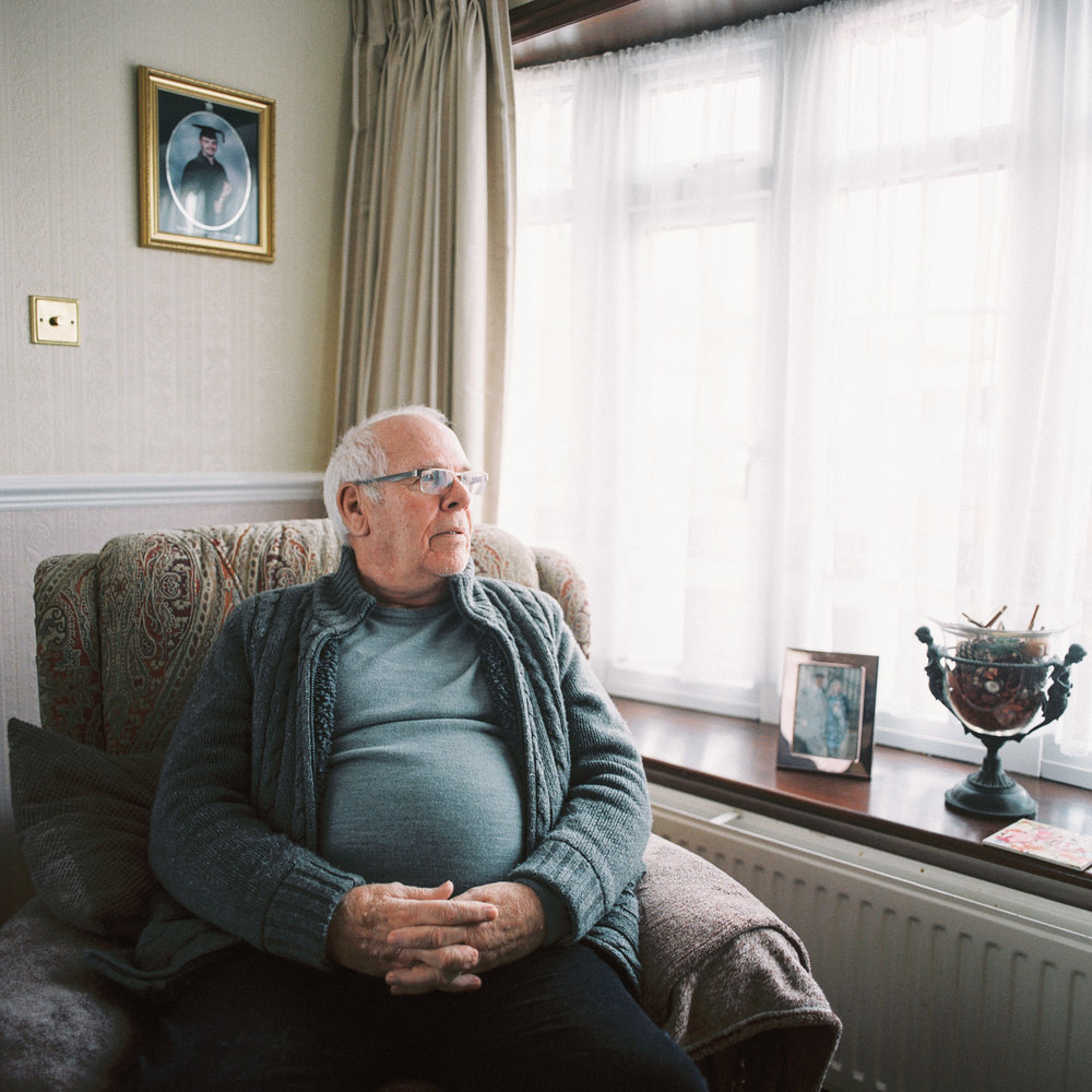 Peter Hewitt MBE sits for a portrait in his living room