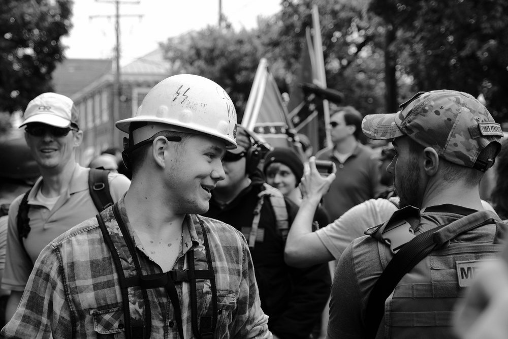 Unite the Right attendees started arriving at Emancipation Park (formerly Lee Park) on Saturday, August 12th, hours in advance of their permitted start time. Despite being provided police protected entry at the rear of the park -- where they would not have come into contact with protesters at all -- many of the white supremacists chose to walk through one of the front entrances. These entrances were guarded by III% militia groups armed with assault rifles and wearing tactical gear. Militia groups like these are generally seen supporting white supremacists such as the man in the white helmet above, who was later seen brutally beating Deandre Harris in a parking garage a couple of blocks away.