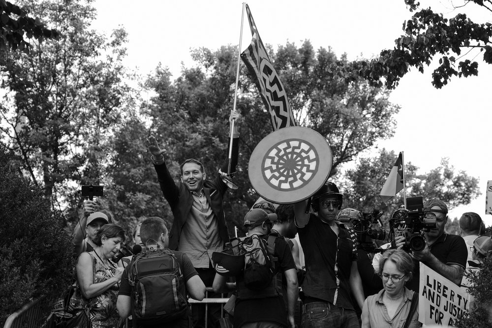 Vanguard America -- the white supremacist group of which James Fields, the alleged murderer of Heather Heyer, appeared to be a member -- made up a significant portion of the early Unite the Right crowd. Vanguard America is part of the Nationalist Front, a US-based neo-Nazi conglomeration that includes the National Socialist Movement (NSM), the Traditionalist Worker Party (TWP), and the League of the South (LoS).  Here, William Fears -- arrested in Gainsville, FL for attempted murder after a speaking engagement by Richard Spencer at the University of Florida on October 19, 2017 -- displays a Nazi salute to the media and crowds of protesters.