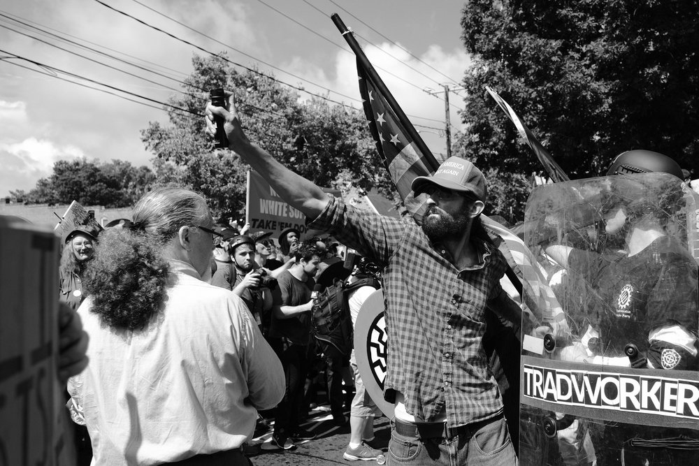 "As they pushed out from their permitted space in the park, the white supremacists used mace and tear gas on the protesters in the street. Seen here is man believed to be Alex Michael Ramos, another of the men that was photographed savagely beating Deandre Harris in the Water Street Garage. Ramos appears to be both a member of the Proud Boys as well as the Georgia III% militia, with which he infamously posed alongside Georgia Senator Michael Williams at a ""March Against Sharia"" rally in Atlanta."